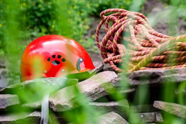Seilzugangsgeräte: schutzhelm, seil, karabiner. bergsteigerausrüstung auf felsen