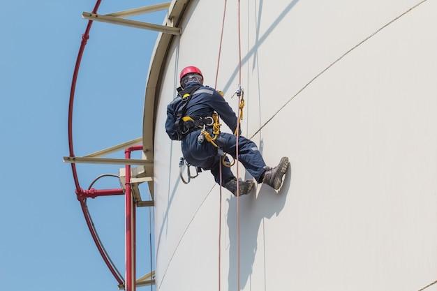 Seilzugangsinspektion für männliche arbeiter in der dickenlagertankindustrie.