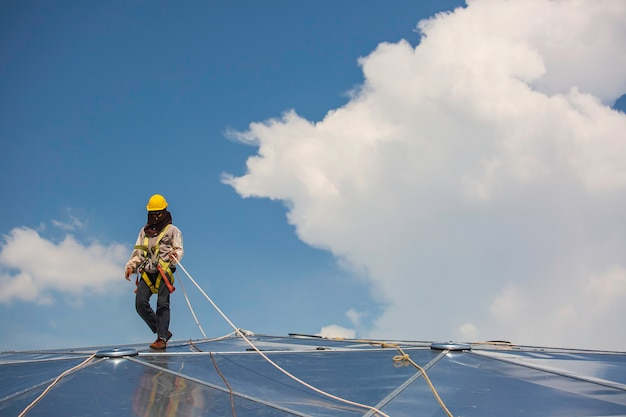 Seilzugangssicherung für männliche arbeiter, die mit einem knotensicherheitsgurt verbunden wird, in dachabsturzsicherung und absturzsicherungs-ankerpunktsysteme einklipsen, bereit für den aufstieg, baustellen-öltankdom