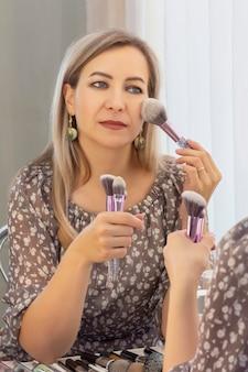 Sein eigener maskenbildner. frau macht make-up vor einem spiegel