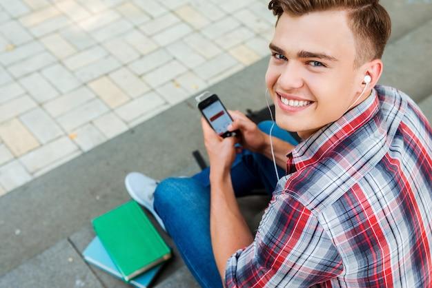 Seine freizeit genießen. draufsicht eines jungen mannes, der mp3-player hört und lächelt, während er an der außentreppe sitzt