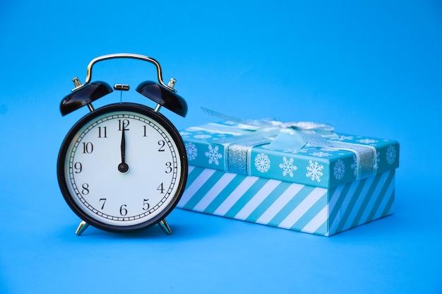 Seine geschenkzeit ein schwarzer retro-wecker und eine blaue geschenkbox sind auf einem blauen isoliert