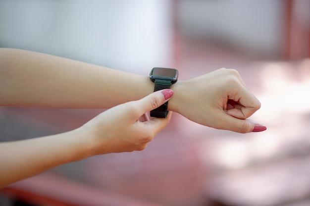 Seine hände und seine schwarze armbanduhr die zeit, das konzept und die zeit kennen