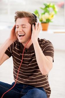 Seine lieblingsmusik hören. glücklicher junger mann mit kopfhörern, der musik hört und die augen geschlossen hält, während er in seiner wohnung auf dem boden sitzt