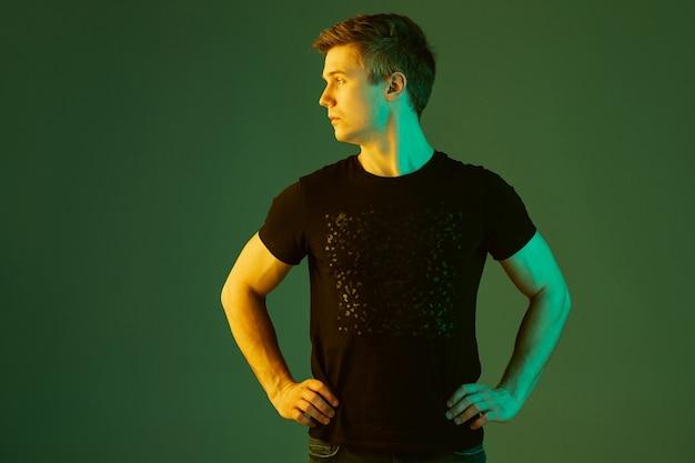 Seite betrachten. porträt des kaukasischen mannes lokalisiert auf grünem studiohintergrund im neonlicht. schönes männliches modell im schwarzen hemd. konzept der menschlichen emotionen, gesichtsausdruck, verkauf, anzeige.