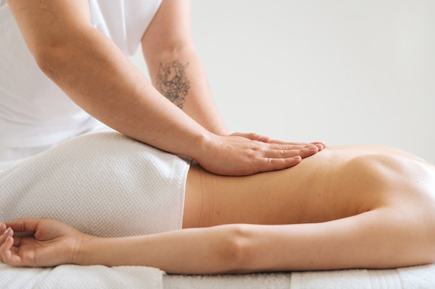 Seite des männlichen masseurs, der den kleinen rücken der jungen frau massiert, die auf dem massagetisch im spa-salon liegt?