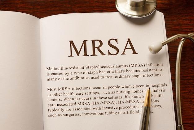 Seite mit mrsa methicillin-resistente staphylococcus aureus-infektion auf dem tisch mit stethoskop, medizinisches konzept