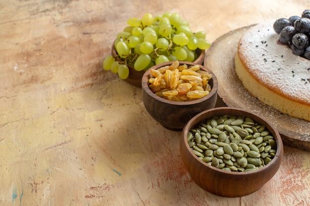 Seite nahaufnahme ansicht ein kuchen schalen von grünen trauben rosinen kürbiskerne ein kuchen auf dem brett