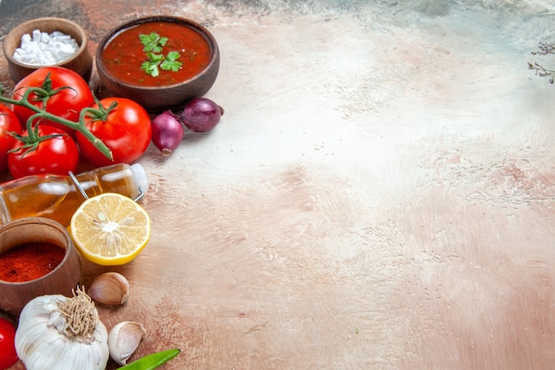 Seite nahaufnahme ansicht gewürze sauce gewürze zwiebeln knoblauch flasche öl tomaten zitrone