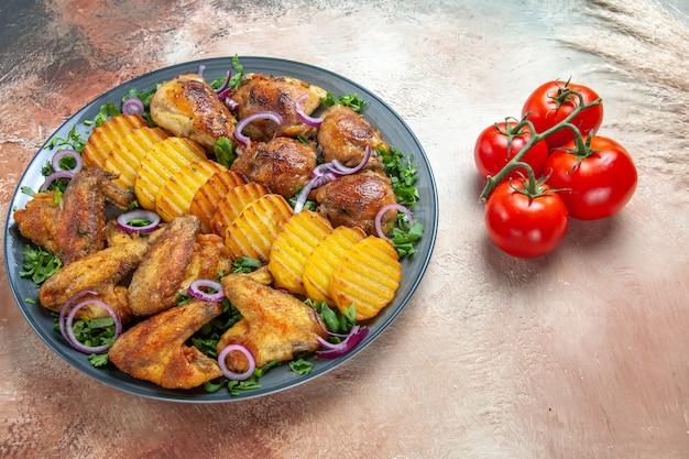 Seite nahaufnahme ansicht huhn hühnerflügel kartoffeln kräuter zwiebeln tomaten mit stielen