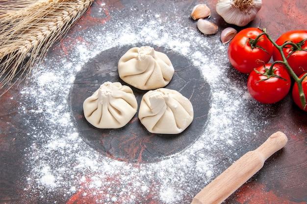 Seite nahaufnahme ansicht mehl khinkali mehl tomaten mit stiel knoblauch nudelholz