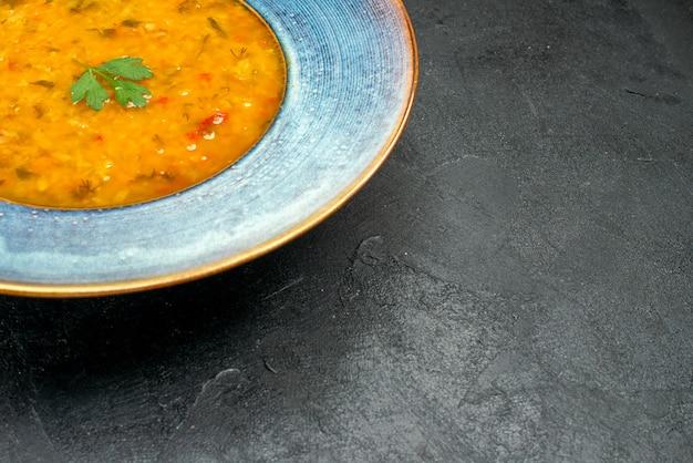 Seite nahaufnahme ansicht schüssel suppe blaue schüssel einer appetitlichen suppe mit kräutern auf dem dunklen tisch