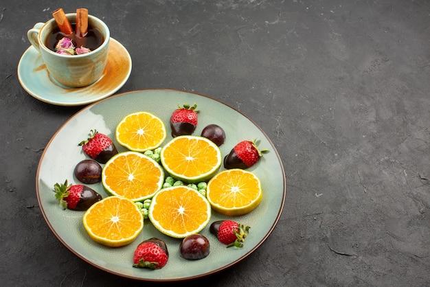 Seite nahaufnahme tasse tee und früchte eine tasse tee mit zimtstangen neben dem obstteller auf dem schwarzen tisch
