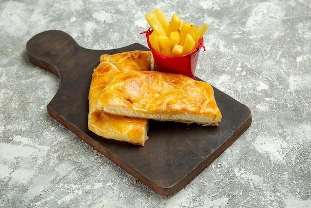 Seite nahaufnahme torten pommes frites pommes und appetitliche torten auf dem küchenbrett auf dem grauen tisch
