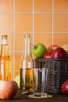 Seitenansicht äpfel im korb mit apfelsaft auf hölzernem und orange fliesenhintergrund. vertikaler raum für text