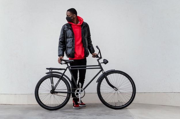 Seitenansicht afroamerikanischer mann und sein fahrrad