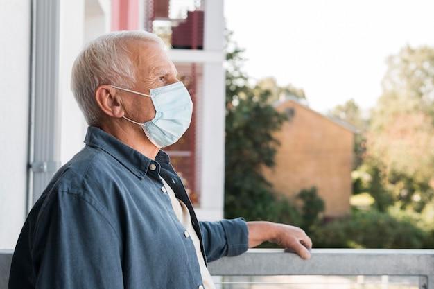 Seitenansicht alter mann, der maske trägt