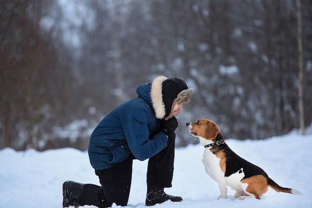 Seitenansicht an einem mann, der amerikanischen beagle-rassenhund auf feld im winter trainiert