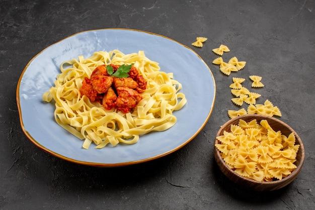 Seitenansicht appetitliche pasta appetitliche pasta mit soße und fleisch auf dem teller neben der schüssel pasta auf dem dunklen tisch