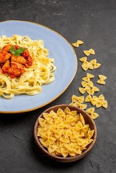 Seitenansicht appetitliche pastaschüssel mit pasta neben dem teller einer appetitlichen pasta mit soße und fleisch auf dem dunklen tisch