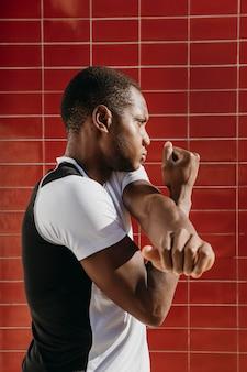 Seitenansicht athletischer mann, der sich ausdehnt
