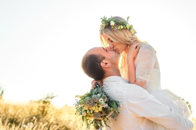 Seitenansicht auf das küssen der braut und des bräutigams an einem sonnigen sommertag hochzeit im freien und beziehungsheep