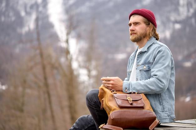 Seitenansicht auf dem jungen kaukasischen mann sitzen sich in der berglandschaft aus tourist männlich