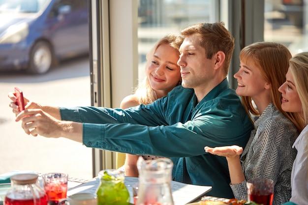 Seitenansicht auf der glücklichen gruppe der jungen kaukasischen freunde, die foto machen