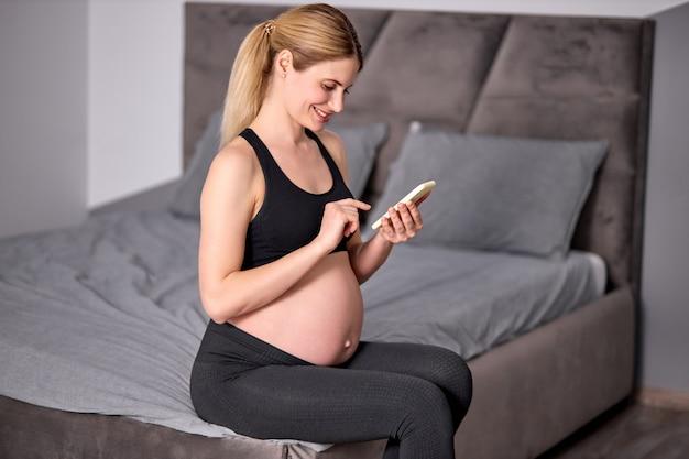 Seitenansicht auf der schönen schwangeren frau, die mit dem handy sitzt und sich ausruht