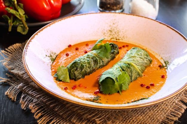 Seitenansicht auf einem gericht der golubtsy gefüllten kohlblätter der osteuropäischen küche mit fleisch oder gemüse, mit saurer sahne und karotte.