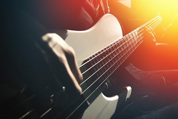 Seitenansicht auf fünfsaitige bassgitarre und hände des musikers, die durch kontrastierendes orangefarbenes licht im dunklen raum beleuchtet werden