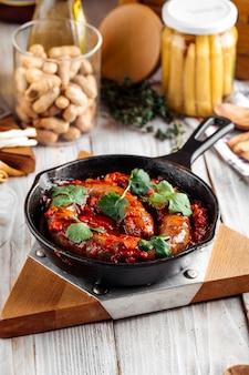 Seitenansicht auf gekochte große wurst in tomatensauce in der gusseisenpfanne