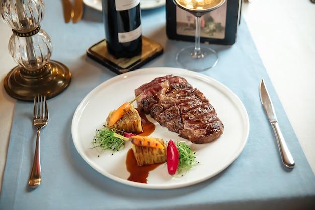 Seitenansicht auf geschnittenem gegrilltem ribeye-steak mit kartoffeln auf weißem teller