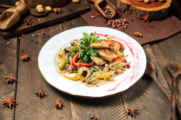 Seitenansicht auf hühnerbrust mit pilzsauce und gemüse