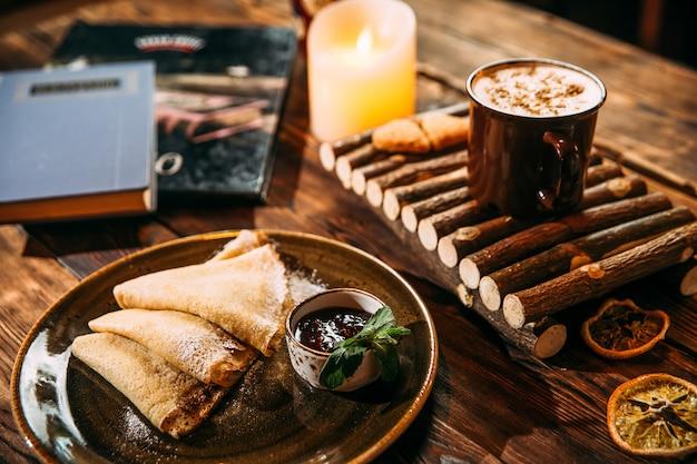 Seitenansicht auf köstlichen wärmenden cappuccino-kaffee mit zimt in einer tasse auf dem holzbrett und pfannkuchen