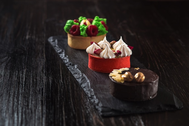 Seitenansicht auf mini-party-törtchen mit frischem obst, schokolade, nüssen und sahne auf schwarzem schieferhintergrund. süße kuchen