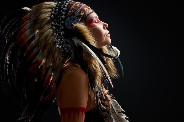 Seitenansicht auf ruhige indische schamanenfrau, die mit geschlossenen augen steht, denkend, in hypnose eingetaucht