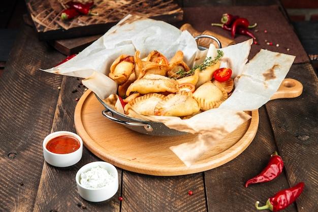 Seitenansicht auf russische snacks mini gebratene kuchen chebureki mit sauce auf dem holztisch