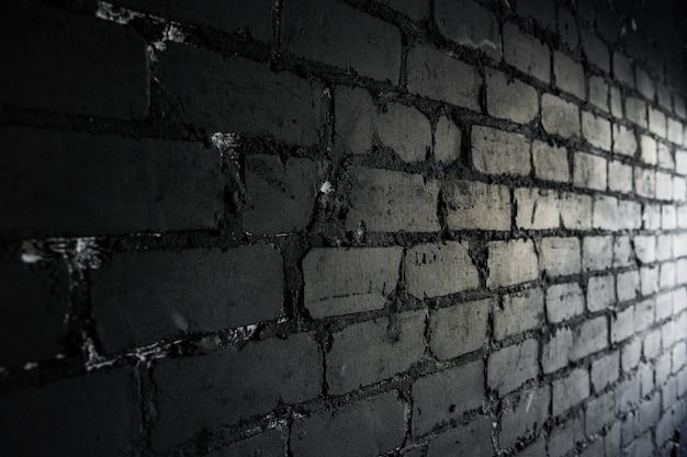 Seitenansicht auf schwarzer backsteinmauer beleuchtet durch licht vom fenster