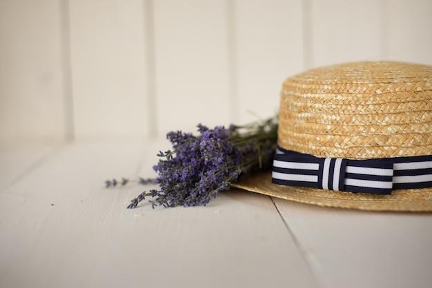 Seitenansicht auf strohhut liegt ein duftender frischer lavendelstrauß. florestischer rahmen.