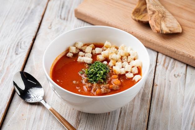 Seitenansicht auf tomatensuppe mit crackern in einer weißen schüssel auf dem holztisch
