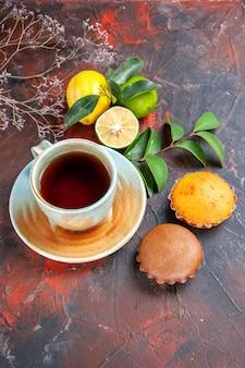 Seitenansicht aus der ferne eine tasse tee eine tasse tee die appetitlichen zitrusfrüchte mit blättern cupcakes