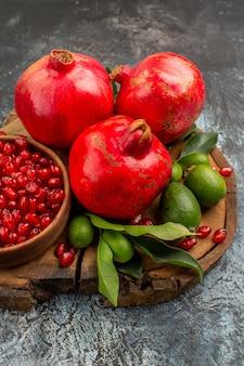 Seitenansicht aus der ferne granatäpfel drei granatapfel mit samen in schüssel auf dem holzbrett