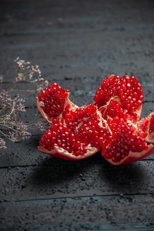 Seitenansicht aus der ferne granatapfel auf tisch roter granatapfel neben ästen auf dunklem hintergrund