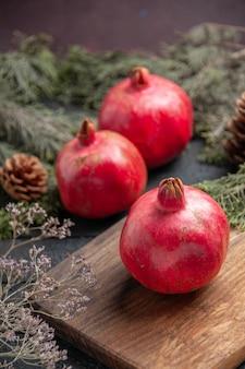 Seitenansicht aus der ferne granatapfel und borded granatapfel auf küchenbrett neben zwei granatäpfeln und fichtenzweigen mit zapfen auf grauem tisch