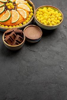 Seitenansicht aus der ferne kuchen und süßigkeiten süßigkeiten in schüssel schokolade und schokoladencreme neben dem kuchen mit limette und schokolade auf dem schwarzen tisch