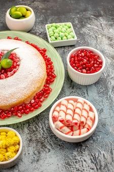 Seitenansicht aus der ferne kuchenbonbons ein appetitlicher kuchen mit granatapfel bunte bonbons zitrusfrüchte