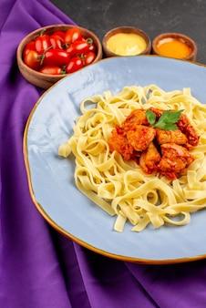 Seitenansicht aus der ferne pasta- und saucenplatte mit pastafleisch und soße zwischen schüsseln mit tomaten und zwei arten von saucen auf der lila tischdecke