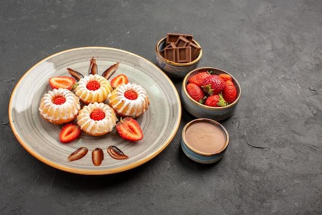 Seitenansicht aus der ferne schokoladen- und keksschalen mit erdbeerschokolade und schokoladencreme neben dem teller mit keksen mit erdbeeren auf dem tisch