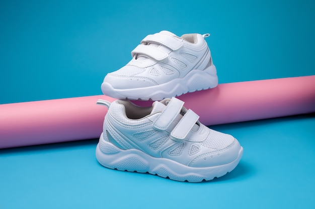 Seitenansicht balance von zwei weißen unisex-sneakern auf einer rosafarbenen langen papierrolle auf blauem hintergrund ein...
